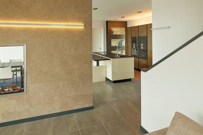Die lange LED-Lichtlinie liefert weiches Raumlicht. In der Küche wird dies durch ein LED-Band auf dem Hochschrank besorgt.