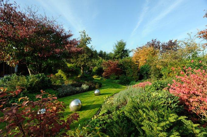 Der sich zwischen den Beeten schlängelnde Rasenweg verleiht dem Garten Großzügigkeit und Tiefe.