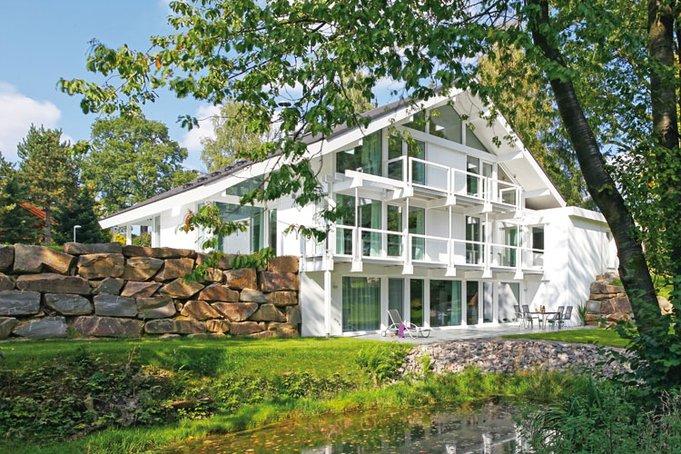 Zeitloses Weiß, üppige Verglasung und eine filigrane Holzkonstruktion prägen die Villa von DAVINCI-Haus.