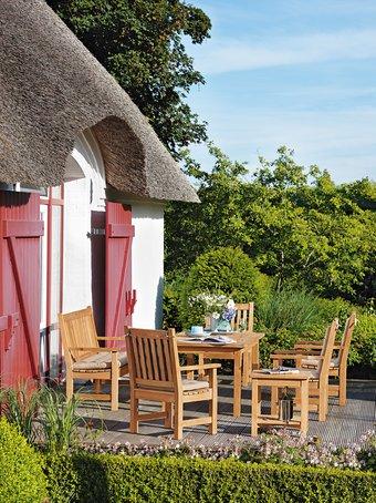 Ein idyllisches Plätzchen vorm Reetdachhaus mit schicken rot lackierten Holztüren, der Bangkirai-Terrasse und Teak-Möbeln (von Garpa).