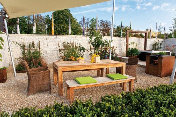 Der Esstisch unterm Sonnensegel wird flankiert von einem Gartengrill, der wie eine Skulptur an seinem Platze ruht.