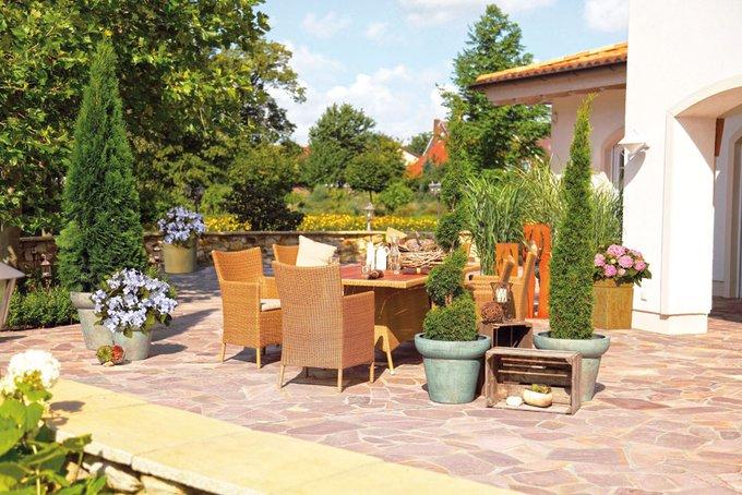 Mit Freunden auf der Terrasse auf gemütlichen Loungemöbeln sitzen, ein leckeres Essen auf dem Tisch, frisch zubereitet in der Outdoorküche.