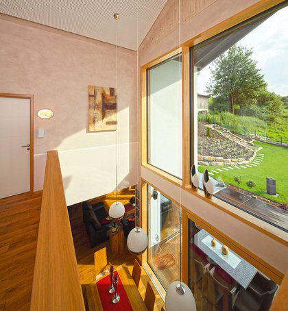 house-2276-blick-von-der-galerie-im-obergeschoss-auf-den-essbereich-im-erdgeschoss-den-garten-sowie-die-angr-2