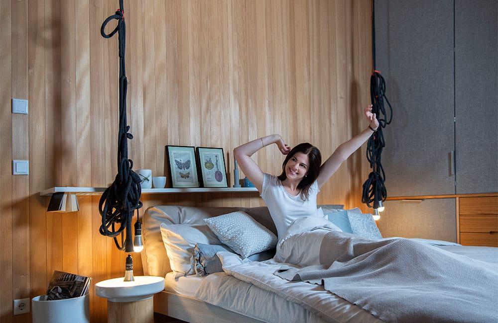 Maßgeschneidert: Schranktüren, die mit Stoff bezogen sind, ein Seilknäuel für die Lampen und ein Regal, in das man seine Bücher aufgeschlagen einhängen kann. Musterhaus Alpenchic von Baufritz.