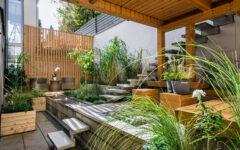 Dekorative Gestaltung eines kleinen Gartens mit Pflanzkübeln aus verschiedenen Materialien.