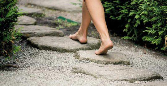 Nackte Füße laufen über einen Naturstein-Gartenweg.